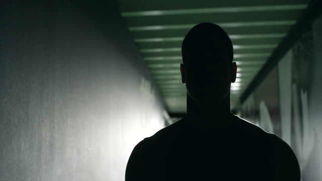 Silhouette of male bodybuilder coming to gym