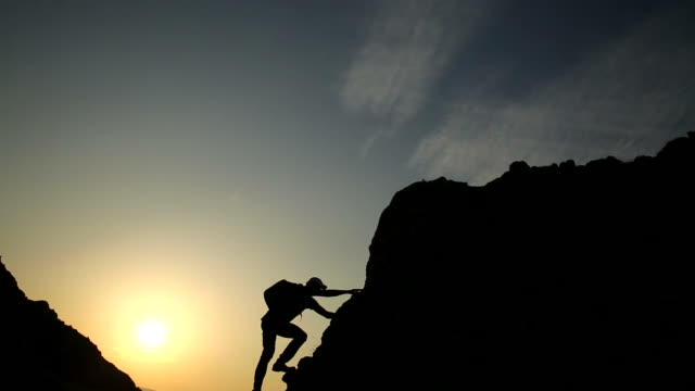 silhouette of male climber against sunset. - free climbing stock videos & royalty-free footage