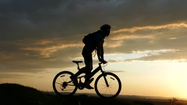 4к silhouette des männlichen mountainbiker bewegen bis zu top - armband stock-videos und b-roll-filmmaterial