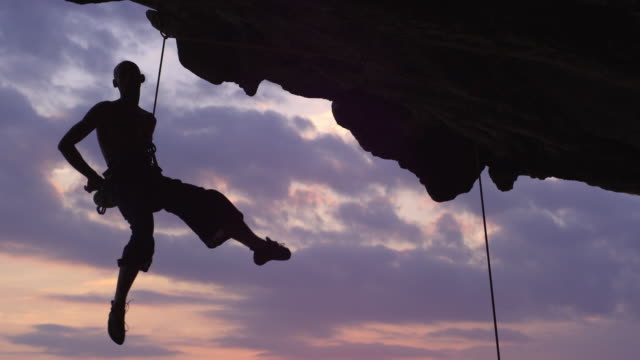 MS Silhouette of male rockclimber hanging under overhanging cliff / Krabi, Thailand
