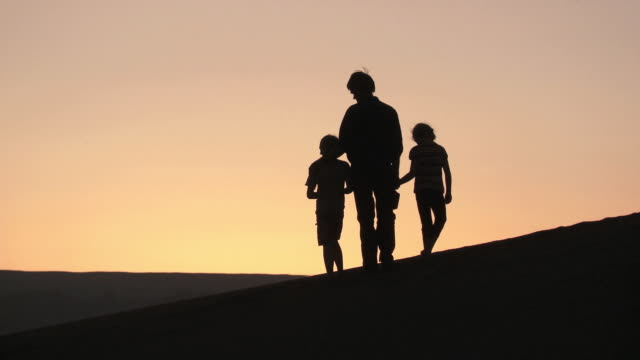 WS Silhouette of man, boy, and girl as they enjoy the sunrise / San Pedro de Atacama, Chile