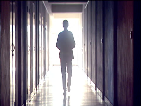 silhouette of man carrying red box walking down corridor towards camera, sunlight beaming through window in background. - silhouette stock videos & royalty-free footage