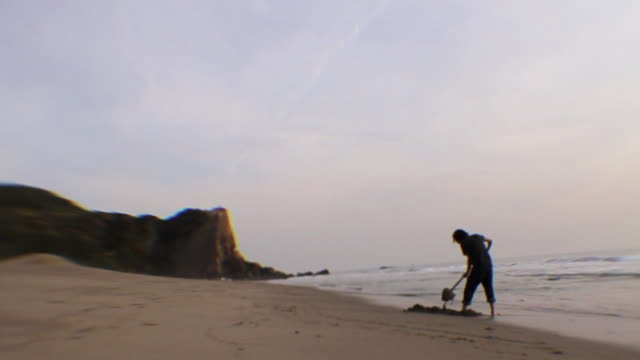 ws silhouette of man digging on beach / los angeles, california, usa - nur junge männer stock-videos und b-roll-filmmaterial