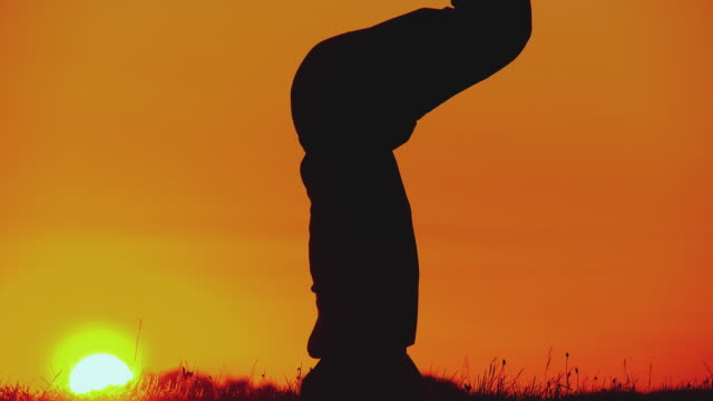 MS TU TD Silhouette of man doing yoga - head stand pose (sirshasana) at sunset, Horjul, Slovenia