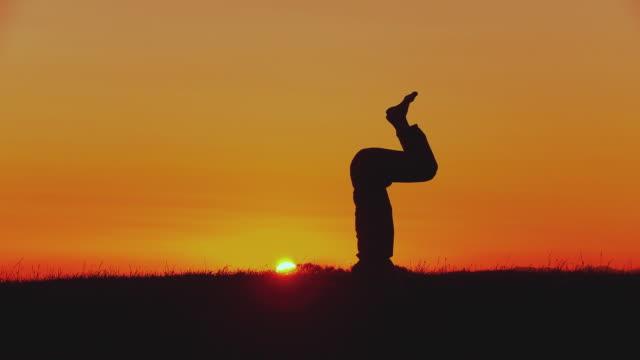 WS Silhouette of man doing yoga - head stand pose (sirshasana) at sunset, Horjul, Slovenia