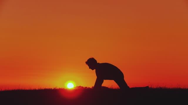 ws silhouette of man doing yoga - sun salutation pose (surya namaskar) at sunset, horjul, slovenia - sun salutation stock videos & royalty-free footage