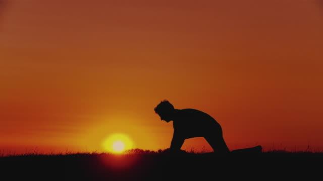 slo mo ws silhouette of man doing yoga - sun salutation pose (surya namaskar) at sunset, horjul, slovenia - sun salutation stock videos and b-roll footage