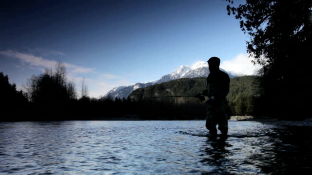 ws silhouette of man fly fishing in cheakamus river, snow capped mountain in background, squamish, british columbia, canada - fishing rod stock videos & royalty-free footage