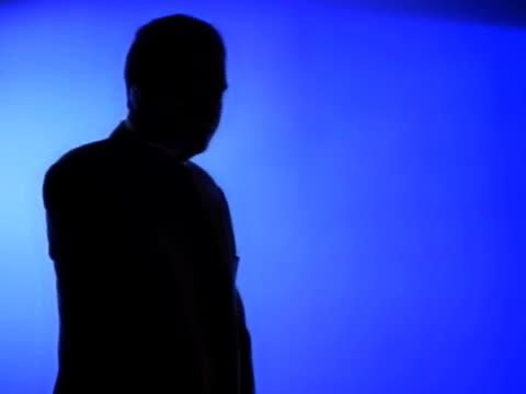 vídeos y material grabado en eventos de stock de silhouette of man in business suit taking a phone call - un solo hombre maduro