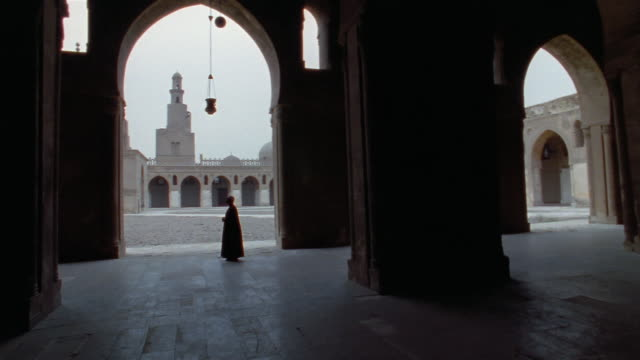 ms, pan, silhouette of man in mosque of ahmad ibn tulum, cairo, egypt - mosque stock videos & royalty-free footage