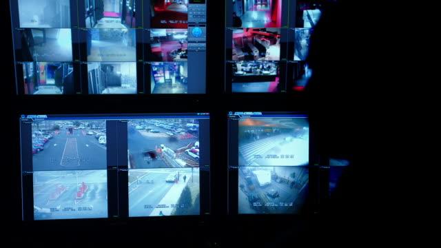 stockvideo's en b-roll-footage met silhouette of man in security office watching video surveillance screens - regelkamer