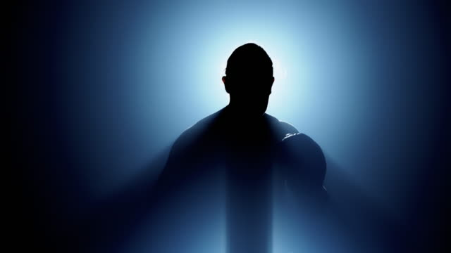 silhouette of man jumping around and punching, getting ready to fight with light behind him, front camera shot. caucasian male. middle shot. - boxing stock videos & royalty-free footage