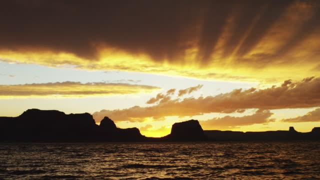 stockvideo's en b-roll-footage met slo mo ws silhouette of man jumping to lake powell at sunset / utah, usa - powellmeer