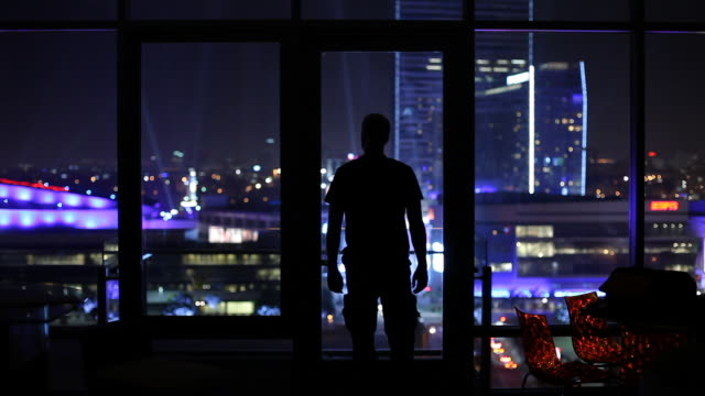 WS Silhouette of man looking through window at city illuminated at night / Los Angeles, California, USA