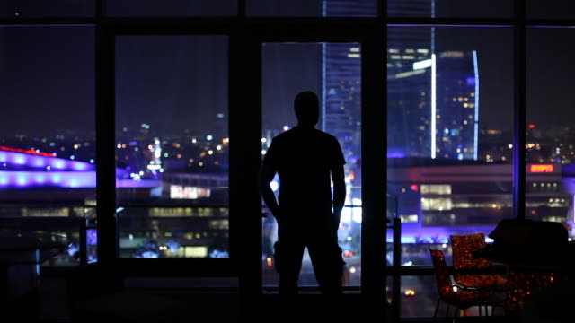 ws silhouette of man looking through window at illuminated city at night / los angeles, california, usa - stare in piedi video stock e b–roll