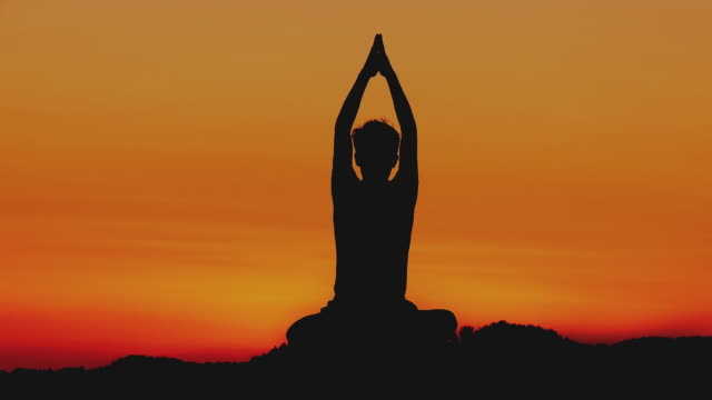 ws silhouette of man meditating in lotus pose at sunset, horjul, slovenia - man sitting cross legged stock videos & royalty-free footage