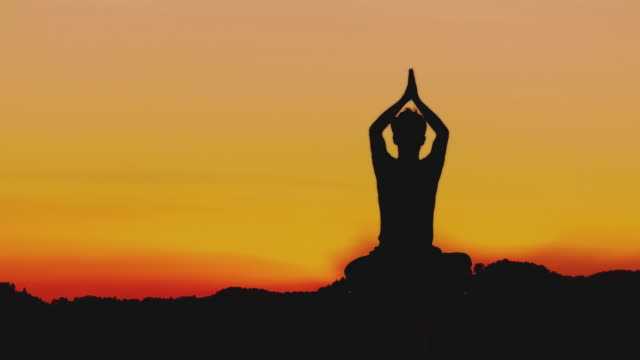 ws silhouette of man meditating in lotus pose at sunset, horjul, slovenia - lotus position stock videos & royalty-free footage