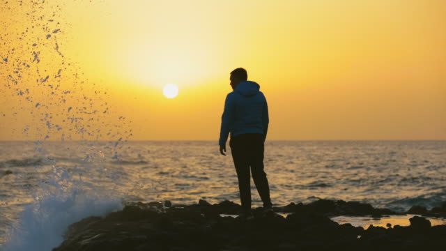 slo mo ws silhouette of man on beach at sunset / canary islands, spain - hooded shirt stock videos & royalty-free footage