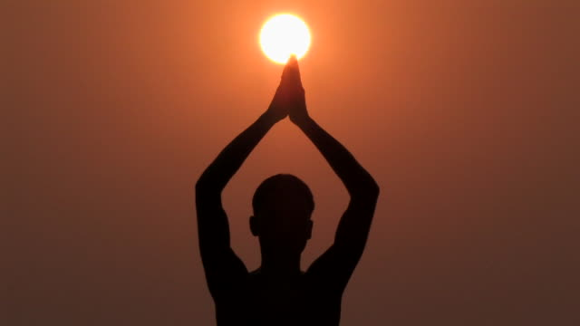 cu, silhouette of man performing yoga against orange sky at sunrise, rear view, varanasi, uttar pradesh, india - pregare video stock e b–roll