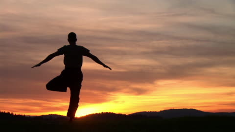 vídeos y material grabado en eventos de stock de ws, silhouette of man performing yoga against sky at sunset, rear view, ljubljana, slovenia - vriksha asana