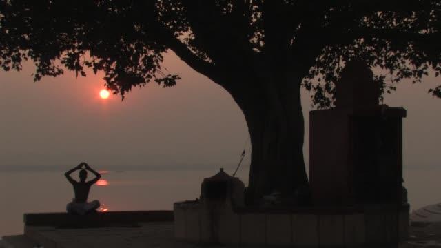 WS, Silhouette of man performing yoga at sunrise, Varanasi, Uttar Pradesh, India