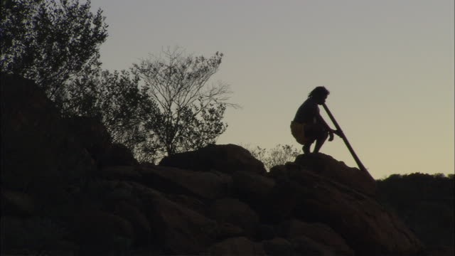 WS DS Silhouette of man playing didgeridoo at dusk, Alice Springs, Northern Territory, Australia