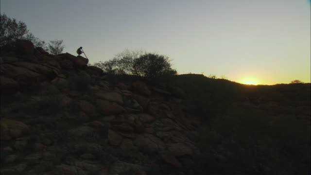 ws ha cs silhouette of man playing didgeridoo at sunset, alice springs, northern territory, australia - australian aboriginal culture stock videos and b-roll footage