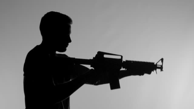 Silhouette of Man Raising Machine Gun in Super Slow Motion