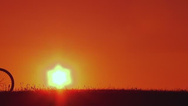 vídeos y material grabado en eventos de stock de slo mo ws silhouette of man riding bicycle at sunset, horjul, slovenia - silueta