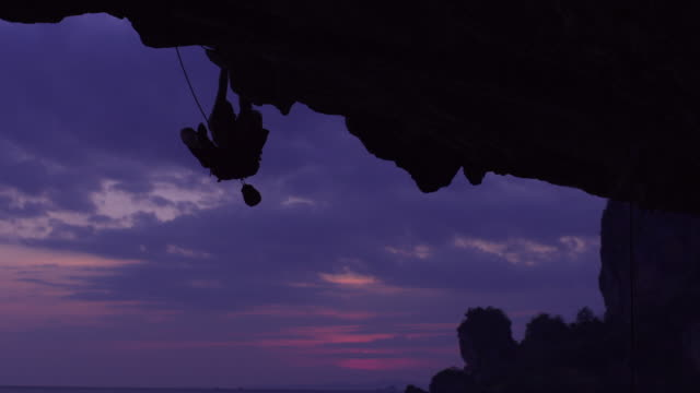 WS Silhouette of man rockclimbing under overhanging cliff, dipping hand in chalk-bag and ascending / Krabi, Thailand