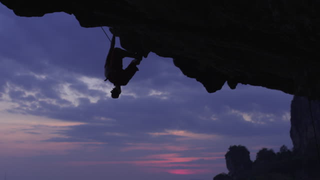 MS Silhouette of man rockclimbing under overhanging cliff, falling and hanging by rope / Krabi, Thailand