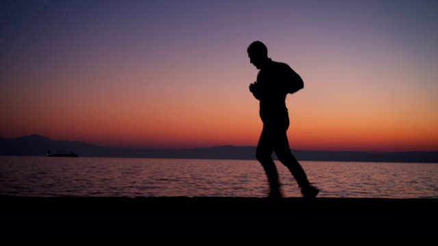 silhouette of man running at sunset - three wheeled pushchair stock videos & royalty-free footage