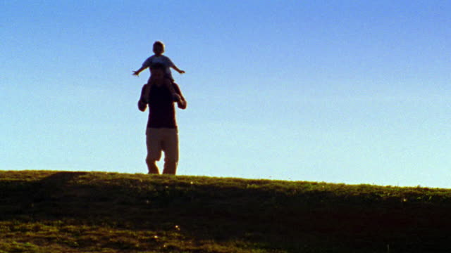 Silhouette of man running with boy on shoulders outdoors