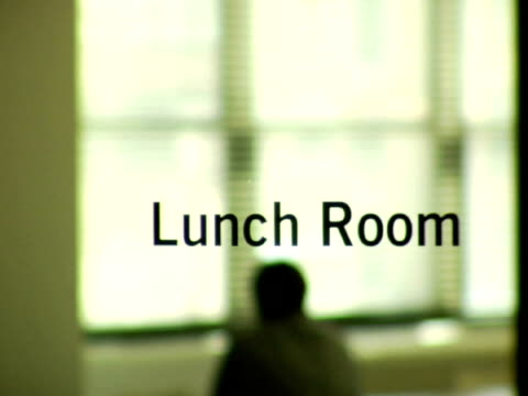 vídeos y material grabado en eventos de stock de ms, r/f, silhouette of man sitting in lunch room in office, rear view - escritura occidental