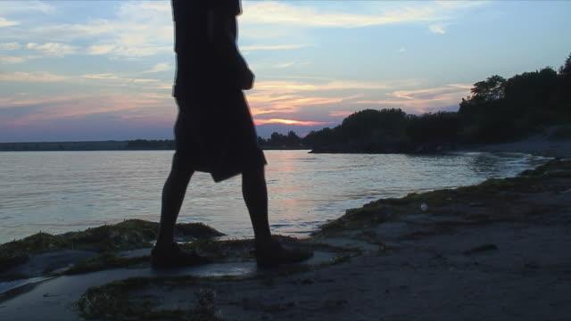 WS Silhouette of man skipping rocks at sunset / Varna, Bulgaria