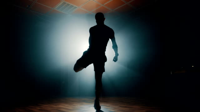 silhouette of man stretching before workout - stretching stock videos & royalty-free footage