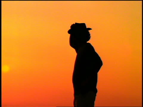Silhouette of man turning + taking off cowboy hat at sunset / Greece