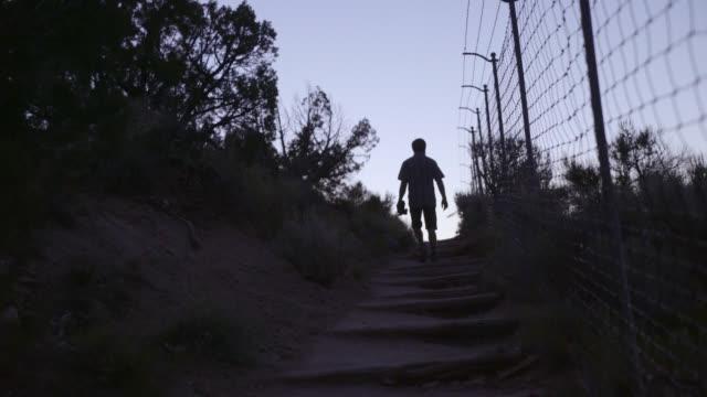 silhouette of man walking along fence - prisoner walking stock videos & royalty-free footage