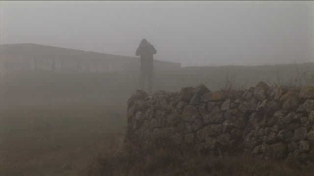 ws, silhouette of man walking in foggy landscape, stone wall in foreground, pancorbo, burgos, spain - stone wall stock videos and b-roll footage