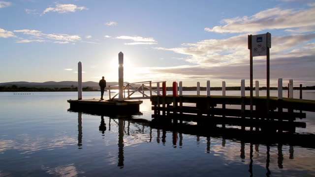 vídeos de stock e filmes b-roll de ws silhouette of man walking onto small jetty / mallacoota, victoria, australia - pontão