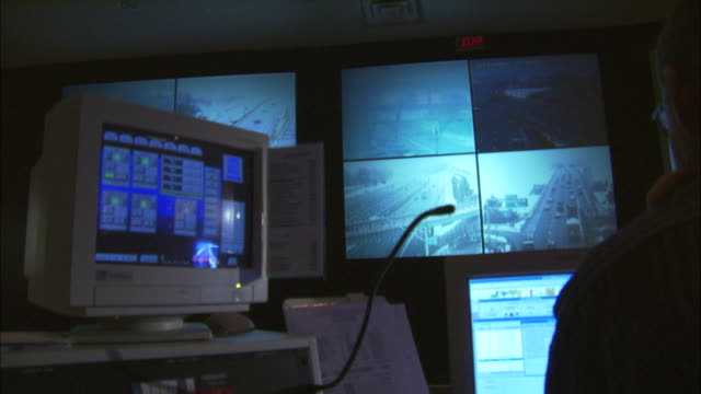 MS, Silhouette of man watching security surveillance monitors in control room, view over the shoulder