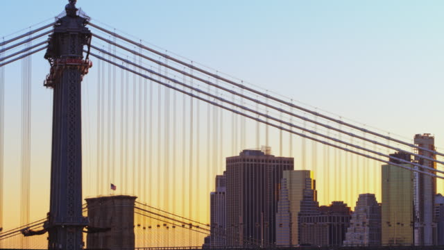 silhouette of manhattan bridge against the golden sky at the sunset. aerial video footage with the panning camera motion. - international landmark stock videos & royalty-free footage