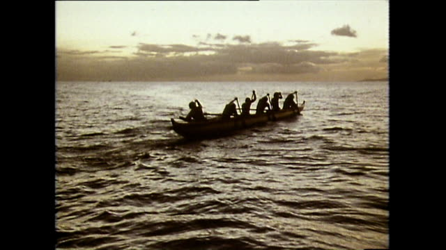 silhouette of men paddling outrigger canoe at sunset; 1983 - hawaii islands stock videos & royalty-free footage