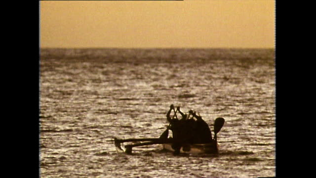 vídeos de stock e filmes b-roll de silhouette of men paddling outrigger canoe at sunset; 1983 - cultura polinésia