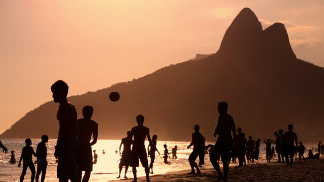 silhouette of men practicing ball tricks at sunset - copacabana stock videos & royalty-free footage