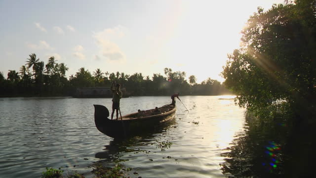 ws silhouette of men propelling tourboat with sticks / cochin, kerala, india - backwater stock videos & royalty-free footage
