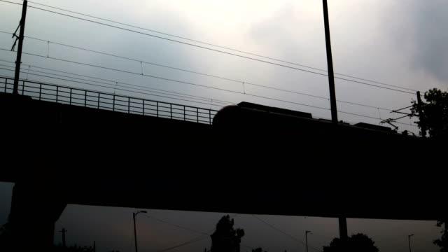 silhouette of metro train crossing over bridge - motorway junction stock videos & royalty-free footage