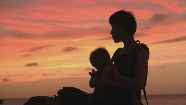 母と娘のビーチのシルエット。 - in silhouette点の映像素材/bロール