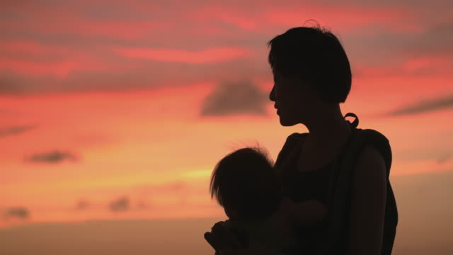 silhouette of mother and daughter on the beach. - back lit stock videos & royalty-free footage