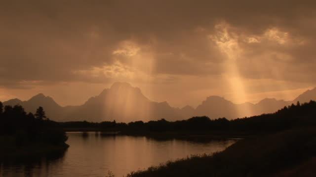 ws, silhouette of mountain range and river with sun shining through clouds, grand teton national park, wyoming, usa - スネーク川点の映像素材/bロール